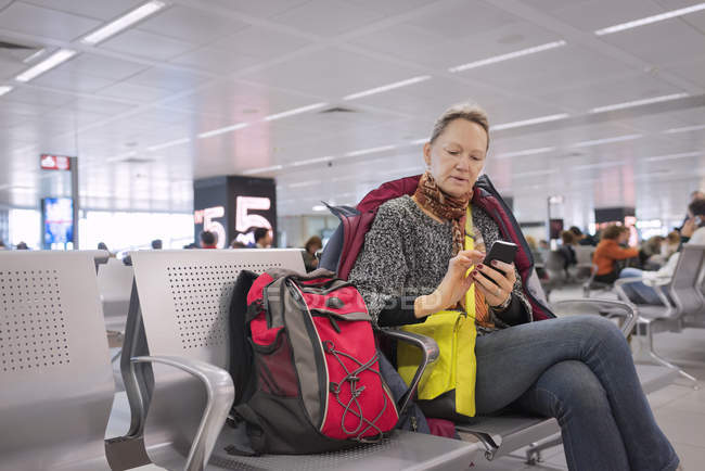 Senior woman texting at airport, people in background — Stock Photo