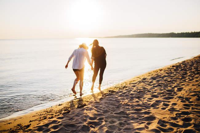 Vista posteriore di due donne che camminano sulla spiaggia — Foto stock