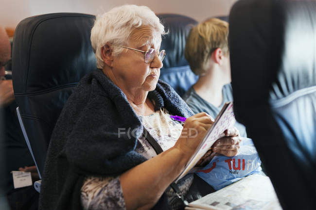 Woman doing crossword on plane, focus on foreground — Fotografia de Stock