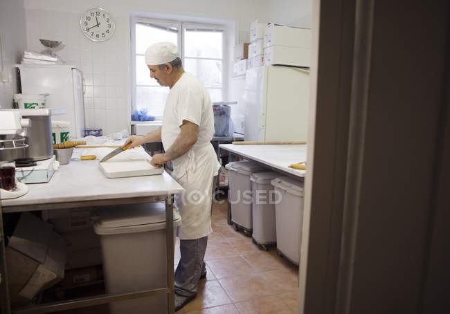Side view of chef cooking at commercial kitchen — Stock Photo