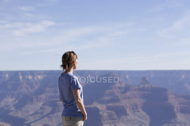 Woman looking at view at Grand Canyon, focus on foreground — Fotografia de Stock