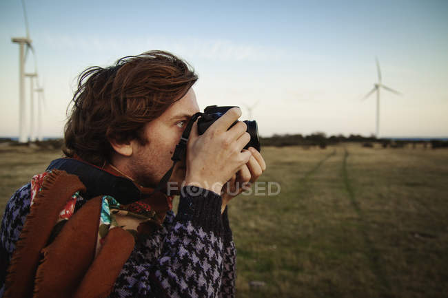 Young man photographing field, focus on foreground — Stock Photo