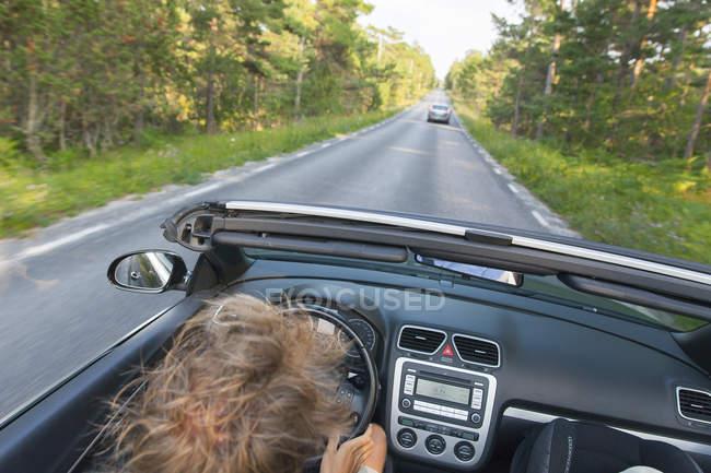 Giovane uomo che guida su strada asfaltata andando lungo la foresta — Foto stock