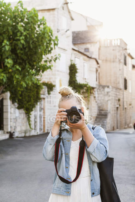 Young woman photographing, focus on foreground — Stock Photo
