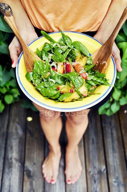 Junge Frau hält Teller mit Salat — Stockfoto
