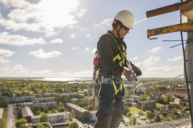 Construction worker in protective workwear high up above city — Stock Photo