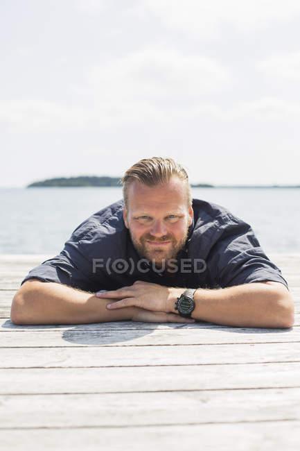 Ritratto di uomo che guarda la macchina fotografica e giace sul molo — Foto stock