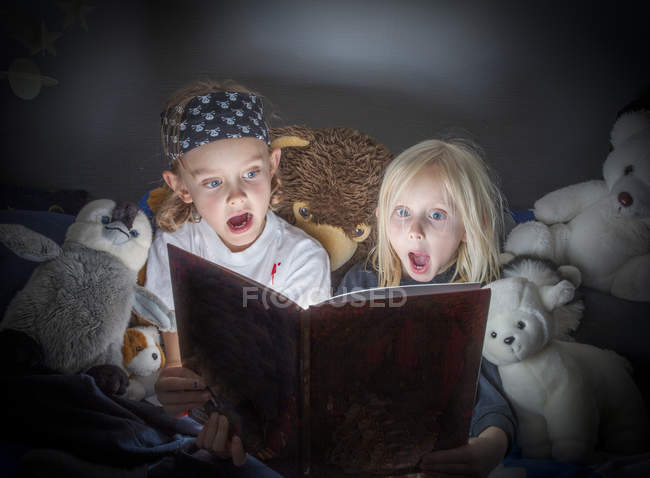 Siblings reading book in bed, selective focus — Stock Photo
