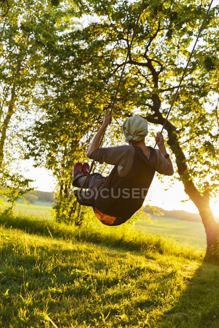 Rear view of senior woman swinging — Stock Photo