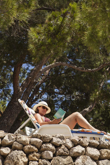 Woman relaxing on sun lounger and reading book — Stock Photo