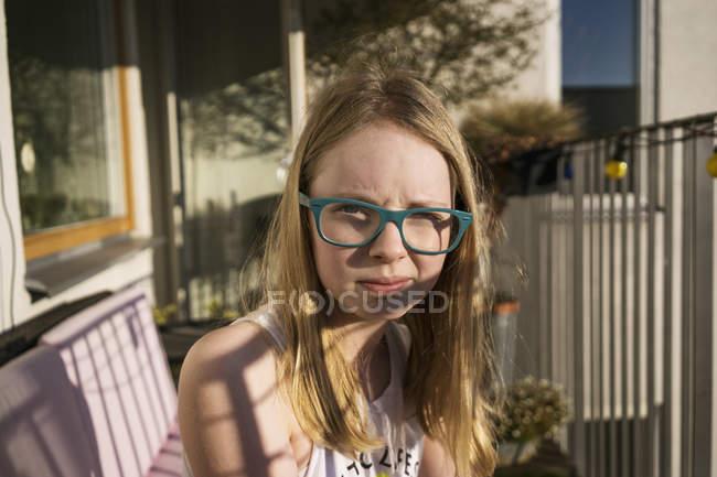 Junges Mädchen mit Brille sitzt draußen — Stockfoto