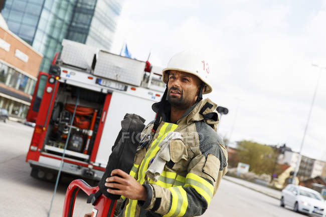Male fire-fighter holding fire hose — Stock Photo