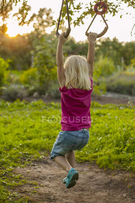 Rear view of girl with blonde hair swinging — Stock Photo