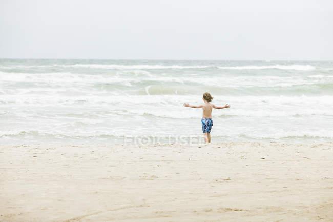 Vista posteriore del ragazzo in piedi sulla spiaggia in Danimarca — Foto stock