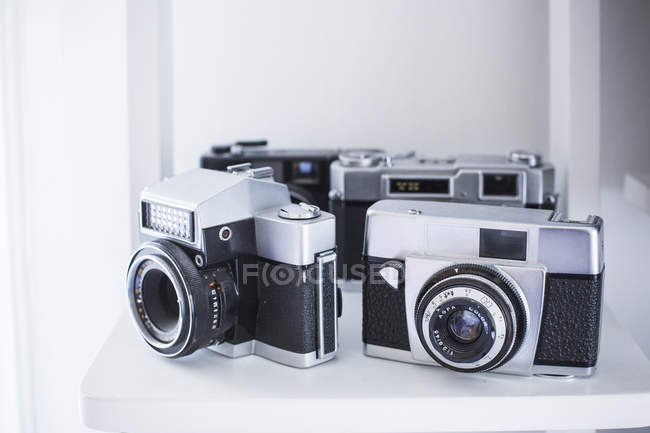 Vintage analogue cameras on white shelf — Stock Photo