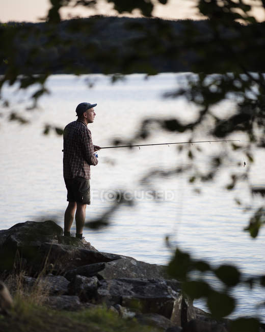 Mid adult man fishing, differential focus — Stock Photo