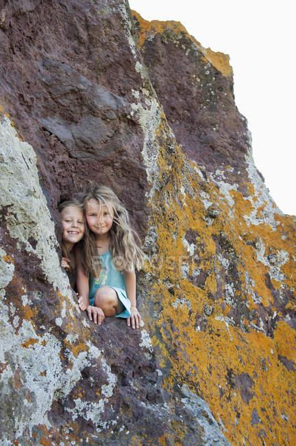 Два молодих дівчат, дивлячись з дірку в скелі — стокове фото