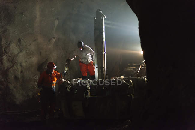 Miners in protective workwear working underground — Stock Photo