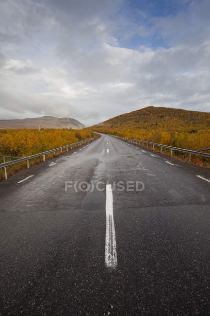 Rural road under sky with clouds in Sweden — Stock Photo