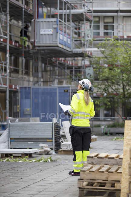 Operaio edile con cianografie che guarda il cantiere — Foto stock