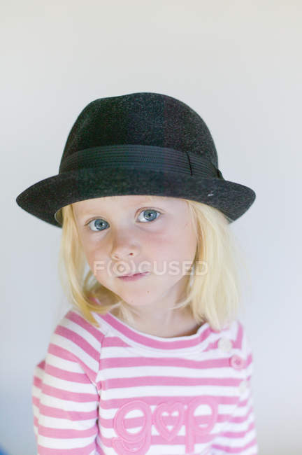 Portrait of girl in black hat looking at camera — Stock Photo