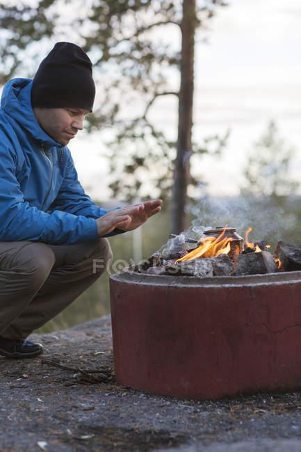 Meio homem adulto agachado pela fogueira, foco diferencial — Fotografia de Stock
