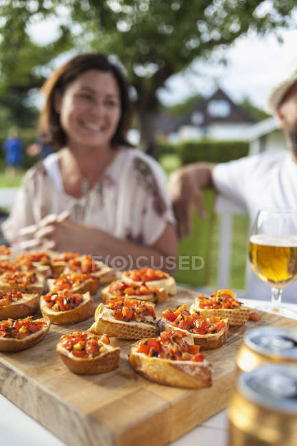 Close-up of snacks, pareja en el fondo, enfoque selectivo - foto de stock