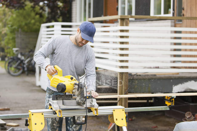 Man working in back yard, focus on foreground — Stock Photo