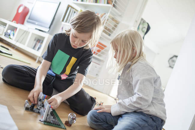 Siblings playing with plastic blocks at living room — Stock Photo