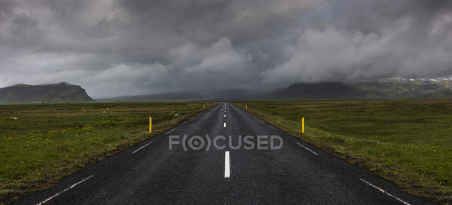 Сельская дорога под грозовые тучи в Исландии — стоковое фото