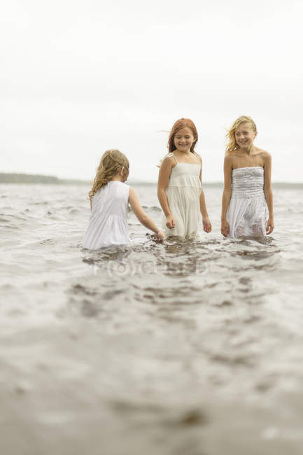 Three girls standing in water, differential focus — Stock Photo