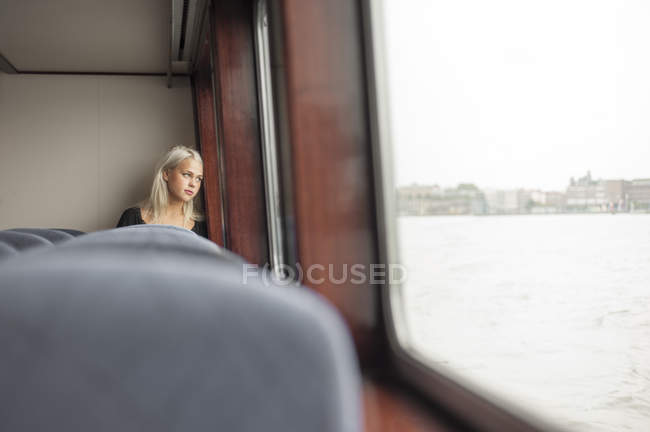 Jeune femme regardant par la fenêtre en train — Photo de stock
