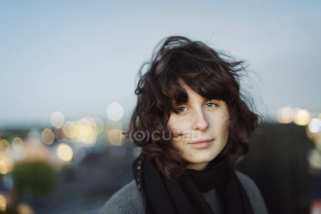 Portrait of young woman at dusk, focus on foreground — Stock Photo