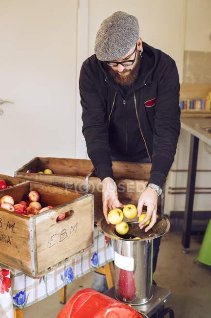 Homem jogando maçãs na imprensa, foco diferencial — Fotografia de Stock