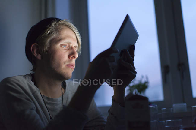 Young man using digital tablet, differential focus — Stock Photo