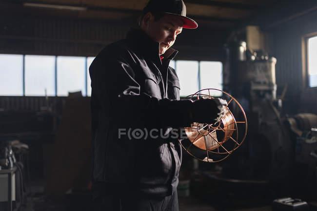 Adolescent, bobinage de fil sur la bobine — Photo de stock