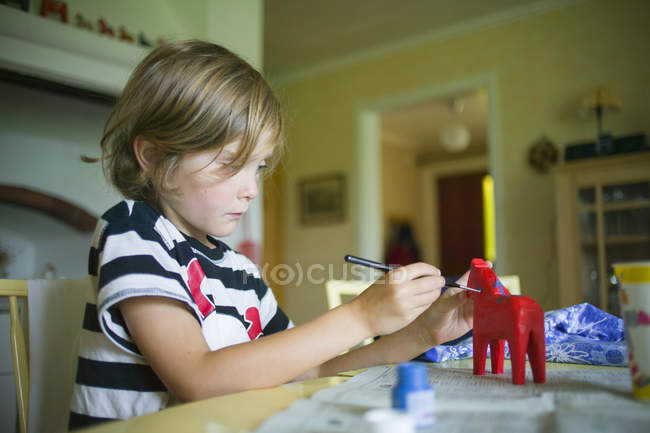 Boy painting horse toy, selective focus — Foto stock