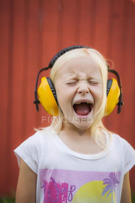 Retrato de menina loira vestindo abafadores de ouvido, gritando com os olhos fechados — Fotografia de Stock