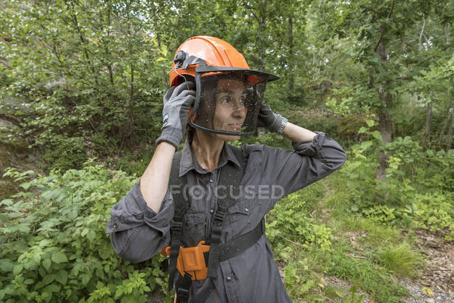 Woman wearing safety gear against garden — Stock Photo