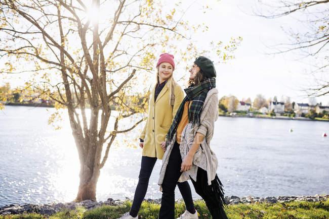 Dos mujeres jóvenes caminando por el canal, se centran en primer plano - foto de stock
