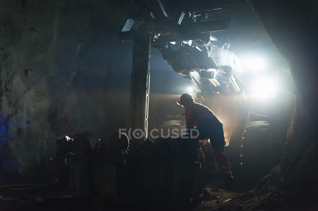 Miner in protective workwear working underground — Stock Photo