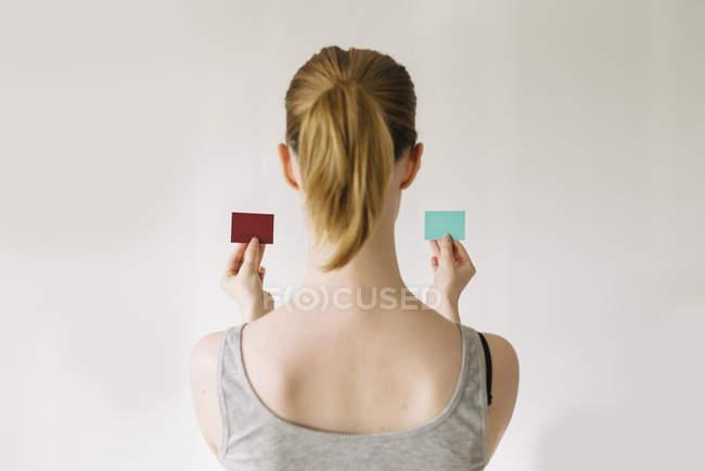 Vue arrière de la femme en comparant des échantillons de couleur contre le mur — Photo de stock