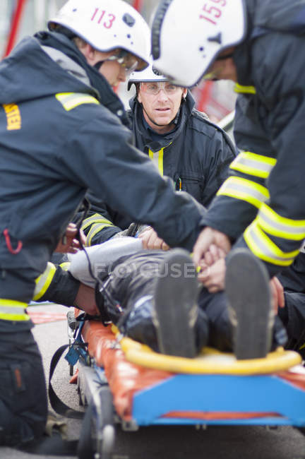 Пожежники згинаючи над людиною лежачи на ношах — стокове фото