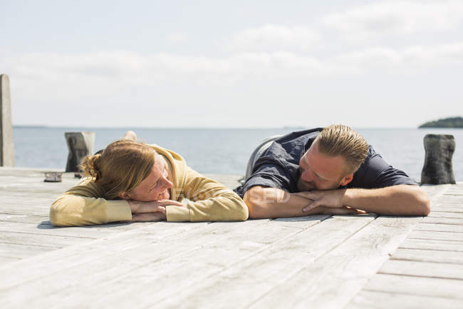 Mature couple looking at each other and relaxing on jetty — Stock Photo