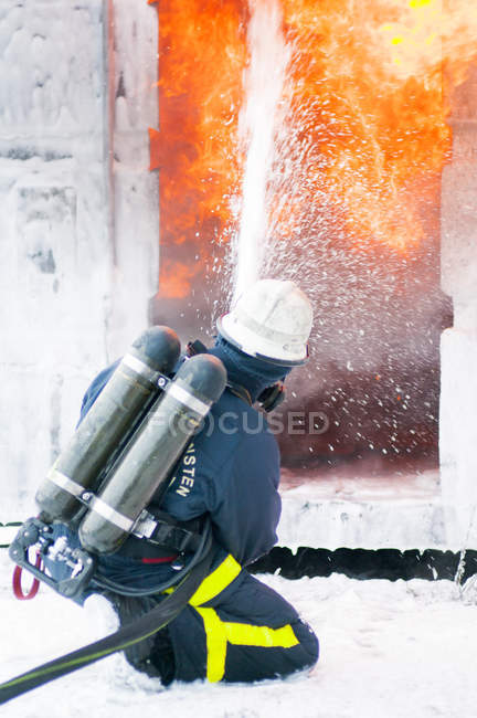 Firefighter spraying foam to stop fire — Stock Photo