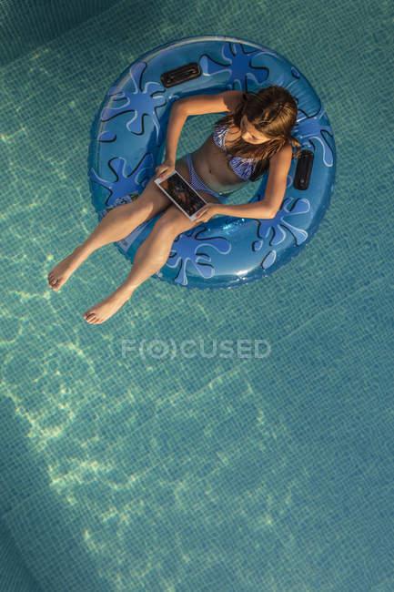 Menina flutuando no anel na piscina e usando tablet digital — Fotografia de Stock