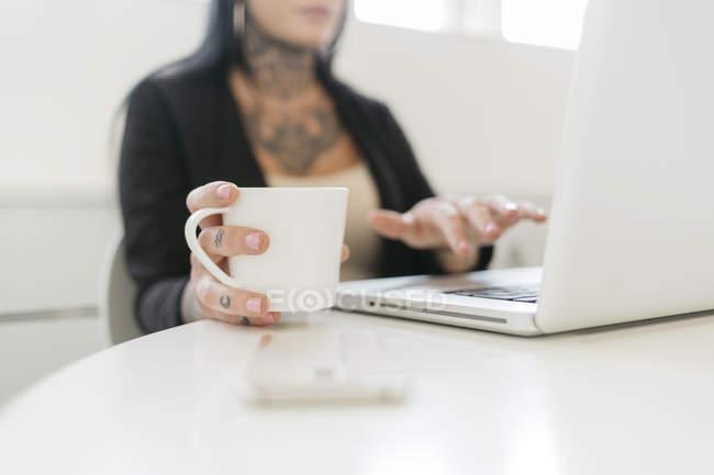Tätowierte Frau hält Becher während sie Laptop benutzt — Stockfoto