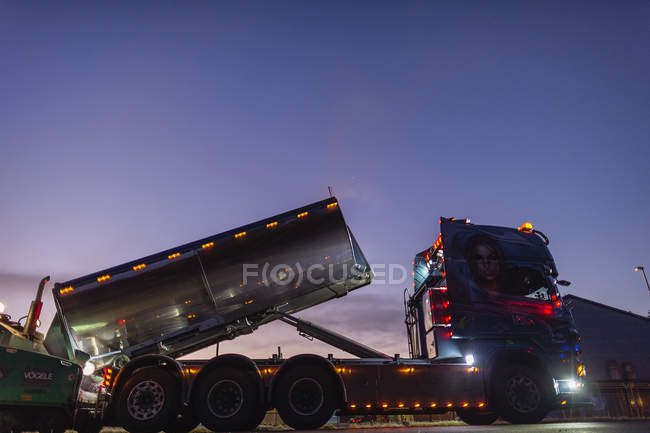 Camion semi illuminé sur la route le soir — Photo de stock