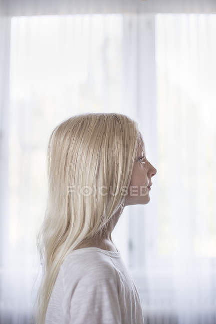 Side view of blonde girl in front of white curtains — Stock Photo