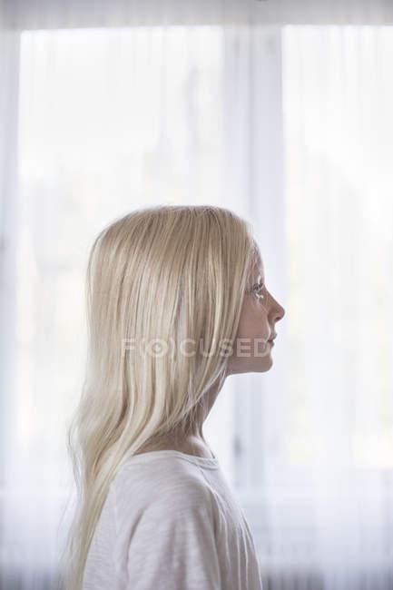 Вид сбоку блондинка перед белые шторы — стоковое фото